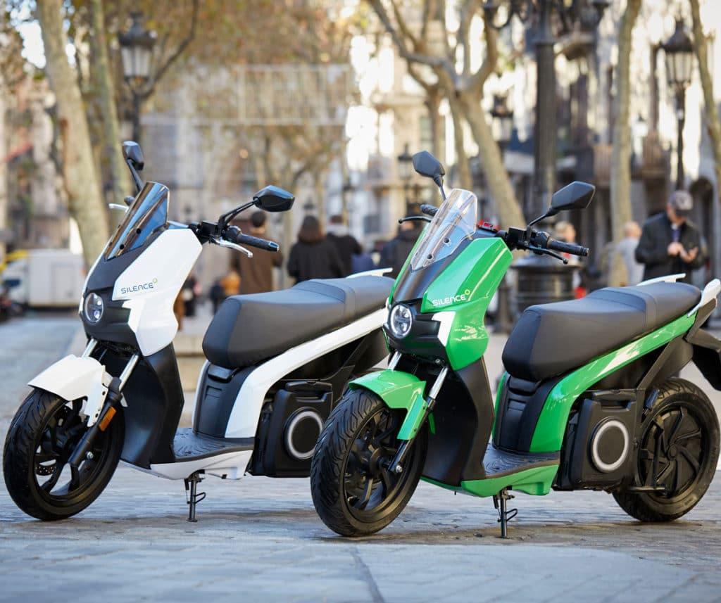 scooters silence S01, un vert et un blanc garés en ville