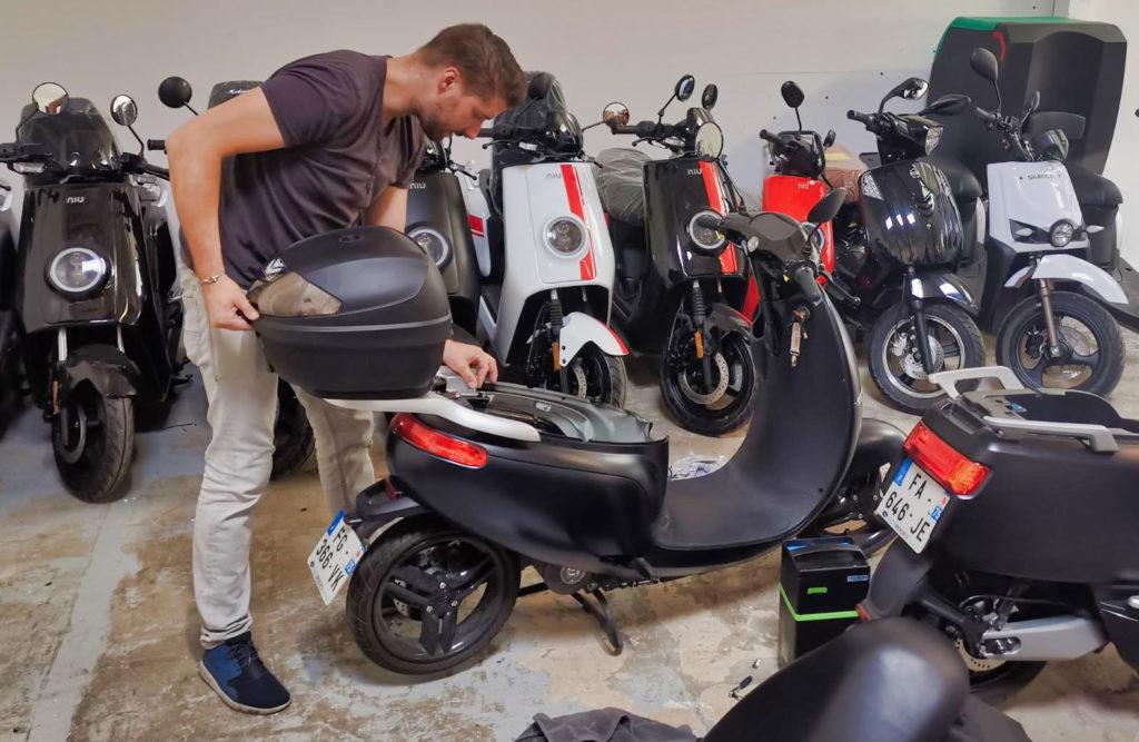 Technicien SAV travaillant sur un scooter de livaison