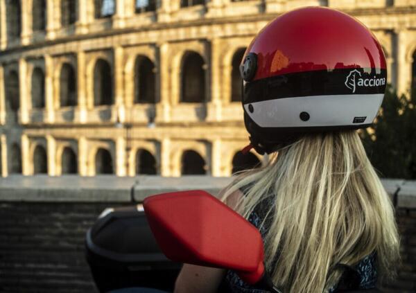 Utilisatrice d'un scooter électrique en libre service devant le Colisée à Rome.