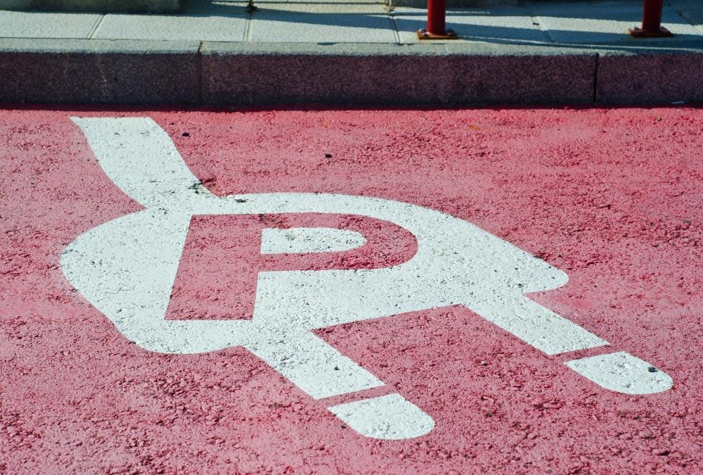 place de parking rouge devant borne de recharge pour scooter électrique